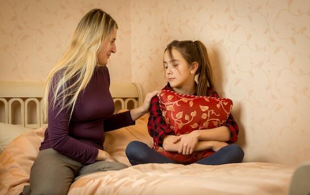 Jovem mãe consolando filha adolescente na cama