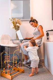 Jovem mãe cuidando de seu filho e teletrabalhando de casa