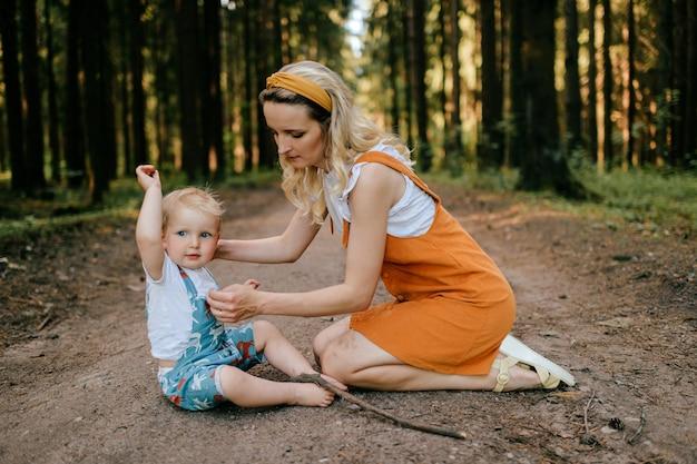 Jovem mãe cuidando de seu filho na floresta