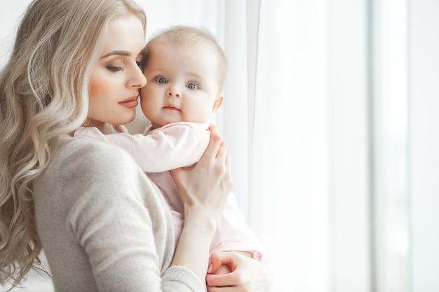 Jovem mãe cuidando de sua filhinha. linda mãe e filha dentro de casa no quarto. família amorosa. mãe atraente, segurando seu filho.