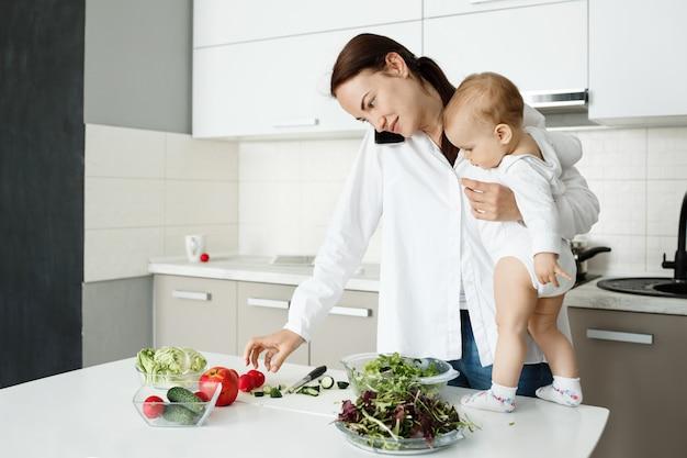 Jovem mãe cuidando de uma criança, falando ao telefone e cozinhando ao mesmo tempo