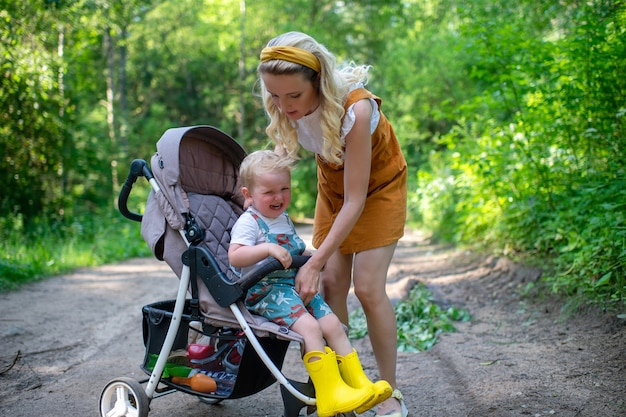 Jovem mãe cuidando do filho chorando sentado no carrinho de bebê na floresta