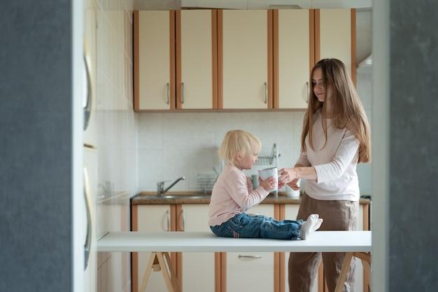 Jovem mãe dá um copo de leite para a filha na cozinha. manhã agradável.
