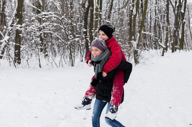 Jovem mãe dando cavalinho na floresta em um dia de inverno