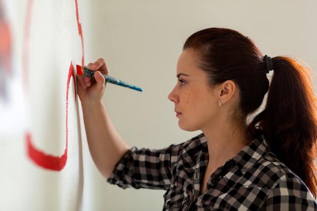 Jovem mãe de cabelos escuros na camisa xadrez desenha em uma parede branca