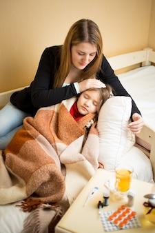 Jovem mãe deitada ao lado da filha doente na cama