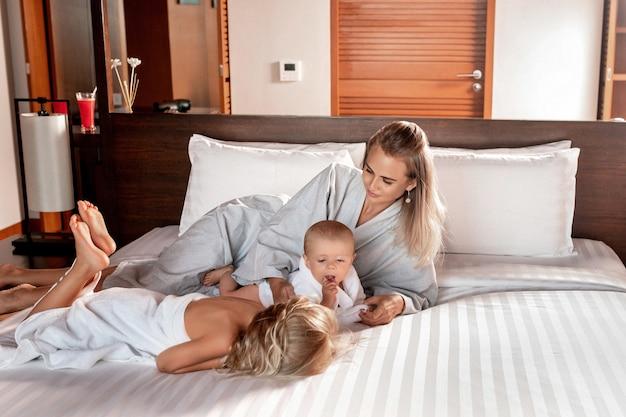 Jovem mãe deitada em uma cama branca com seus filhos