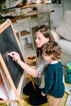 Jovem mãe desenhando giz na lousa com seu filho pequeno em casa