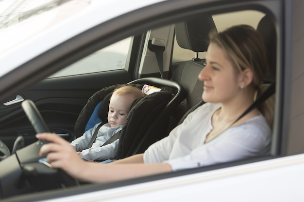 Jovem mãe dirigindo carro com seu filho sentado no carro na cadeira de bebê