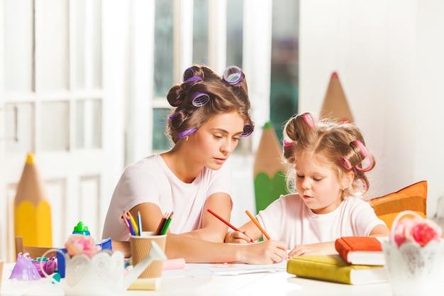 Jovem mãe e a filha pequena desenhando a lápis em casa