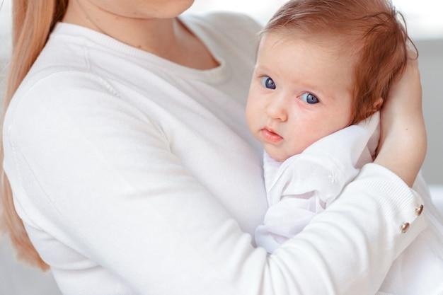 Jovem mãe e bebê recém-nascido no quarto branco