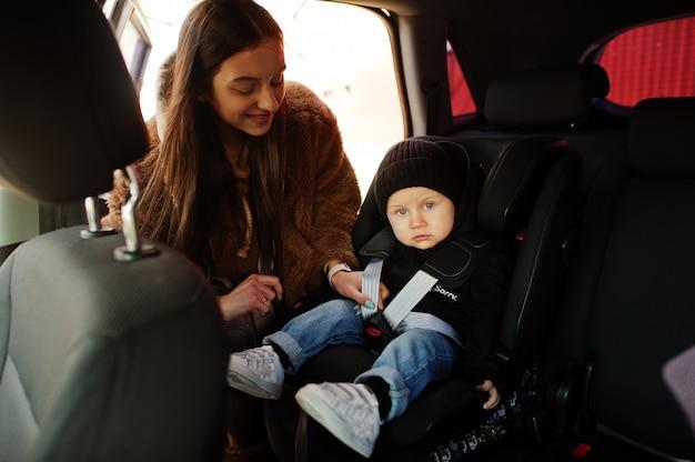 Jovem mãe e criança no carro. cadeira de bebê na cadeira. conceito de condução de segurança.