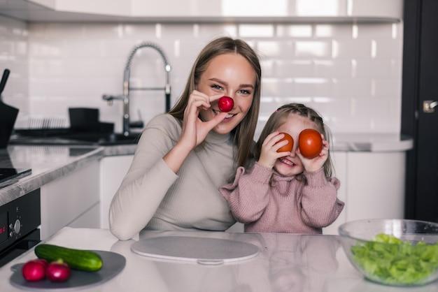 Jovem mãe e criança preparando comida saudável e se divertindo na cozinha