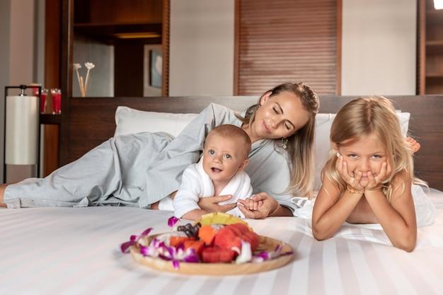 Jovem mãe e dois filhos deitados na cama com um prato de frutas tropicais