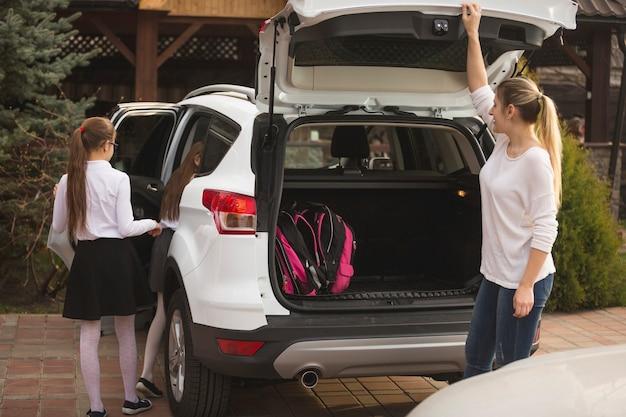 Jovem mãe e duas filhas entrando no carro para ir para a escola