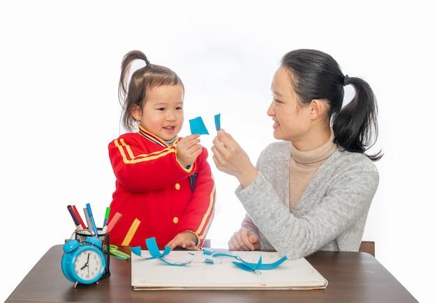 Jovem mãe e filha brincando de corte de papel