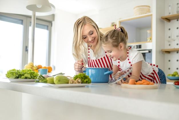 Jovem mãe e filha caucasiana usando aventais combinando, cozinhando sopa juntas em uma cozinha