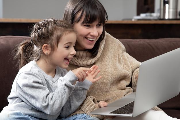 Jovem mãe e filha com o laptop em casa sentado no sofá, sentindo alegria, aproveitando o tempo juntos.