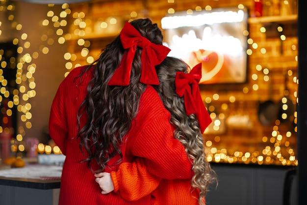 Jovem mãe e filha com um cabeleireiro encaracolado e grandes laços vermelhos de natal