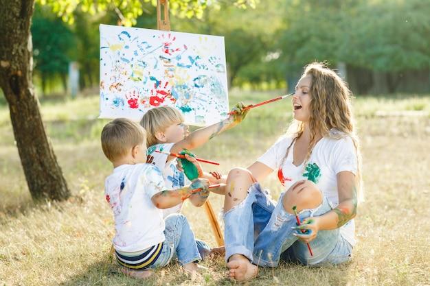 Jovem mãe e filha desenhando um ao outro. família feliz ao ar livre