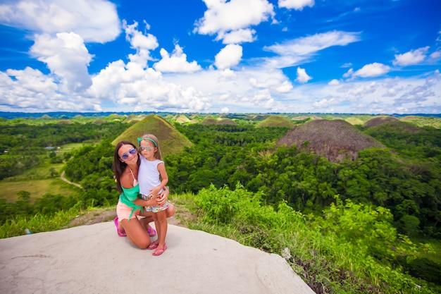 Jovem mãe e filha em excursão para as colinas de chocolate