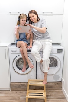 Jovem mãe e filha estão brincando com tablet na lavanderia, sentado na máquina de lavar