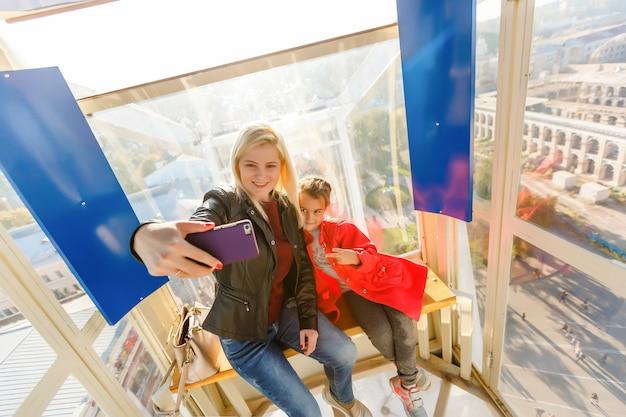 Jovem mãe e filha garota tomando selfie enquanto na roda gigante