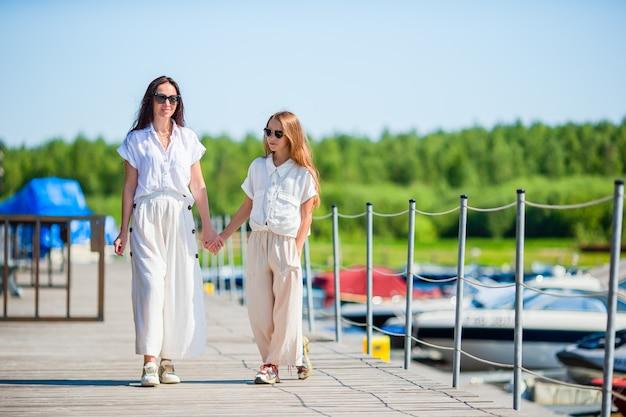 Jovem mãe e filha no porto no verão