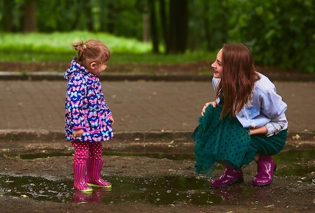 Jovem mãe e filha se divertir andando em gumboots nas piscinas no parque