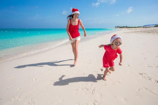 Jovem mãe e filha se divertir na praia tropical