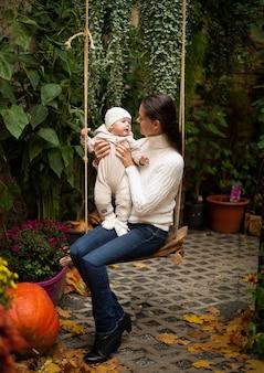 Jovem mãe e filha sentadas no balanço ao lado da abóbora, véspera de halloween