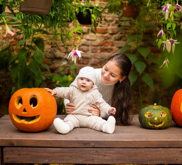 Jovem mãe e filha sentadas perto de abóboras, véspera de halloween