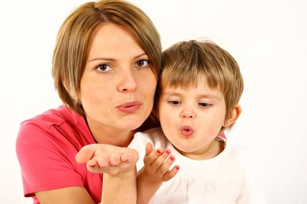 Jovem mãe e filha sobre o branco mandando beijos