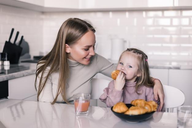 Jovem mãe e filha tomando café na mesa da cozinha