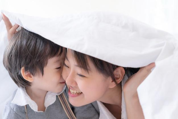 Jovem mãe e filho debaixo do cobertor com felicidade