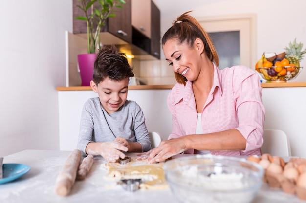 Jovem mãe e filho filho bonitinho preparando a massa, assar biscoitos e se divertindo na cozinha.