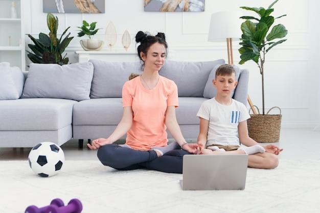 Jovem mãe e filho praticando ioga com o laptop na frente deles