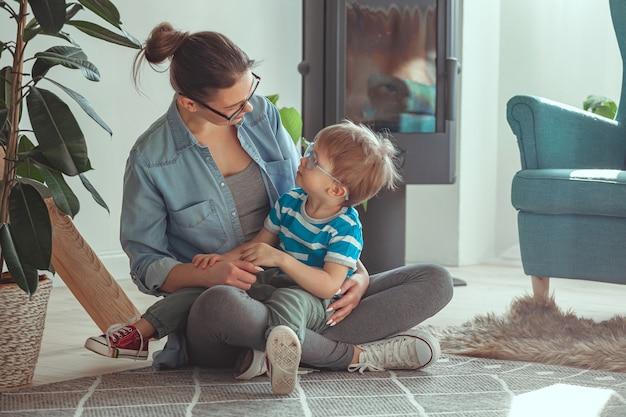 Jovem mãe e filho se abraçando, sentados no chão em casa