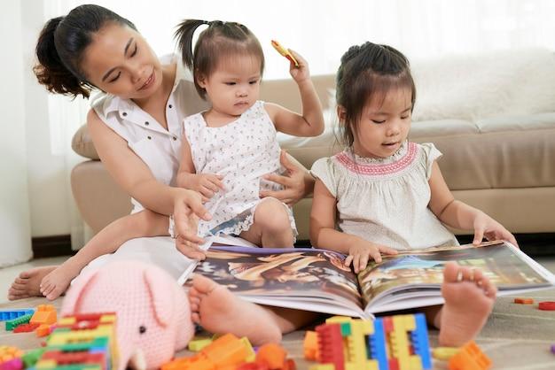 Jovem mãe e filhos brincando com brinquedos e olhando fotos no álbum quando passam o dia em casa devido ...