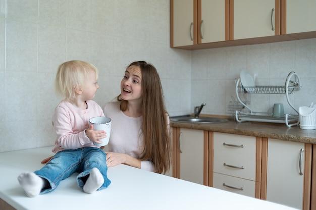 Jovem mãe e menina bonitinha comunicação de manhã na cozinha.