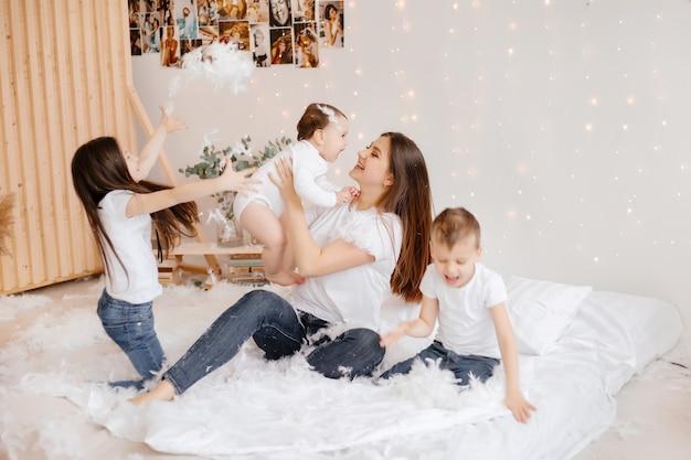 Jovem mãe e seus três filhos em jeans e camisetas estão brincando e se divertindo sentados no chão