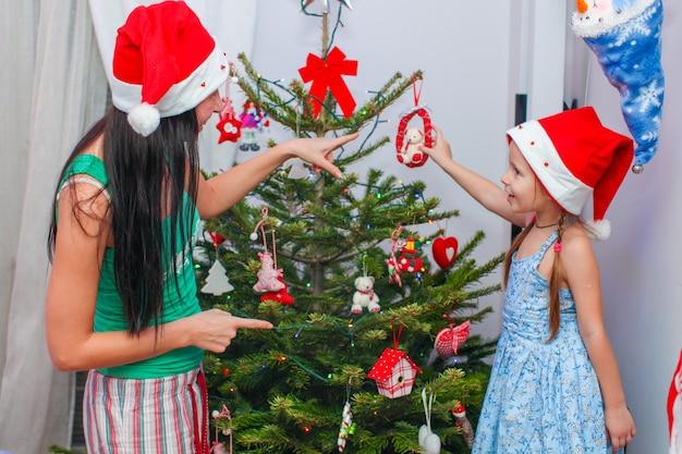 Jovem mãe e sua adorável menina de chapéu de papai noel decoram sua árvore de natal