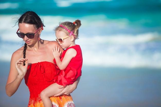Jovem mãe e sua filha andando na praia tropical