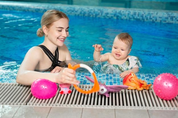 Jovem mãe e sua filha bebê brincam na piscina.