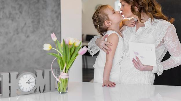 Jovem mãe e sua filha beijando uns aos outros em casa