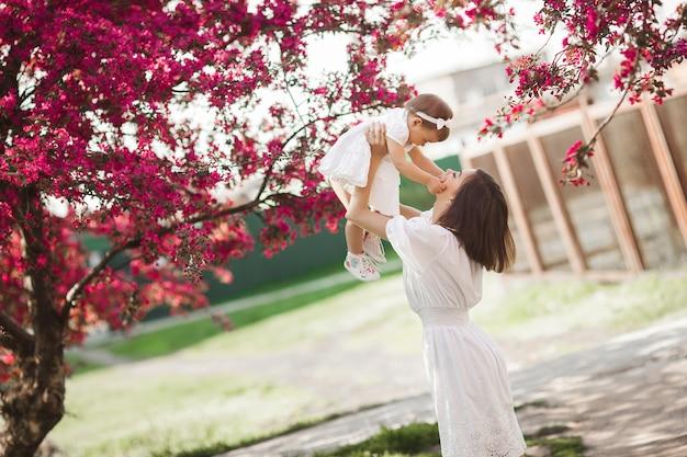 Jovem mãe e sua filha caminhando juntos no parque na primavera. família feliz ao ar livre. amar com a adorável menina.