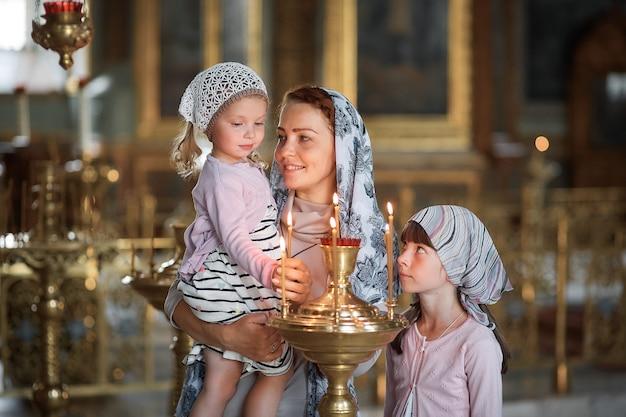 Jovem mãe e sua filha caucasiana loira com velas na igreja ortodoxa russa