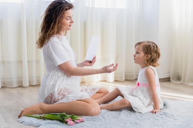 Jovem mãe e sua filha doce sentado no tapete em casa
