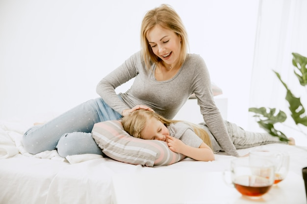 Jovem mãe e sua filha em casa em uma manhã ensolarada