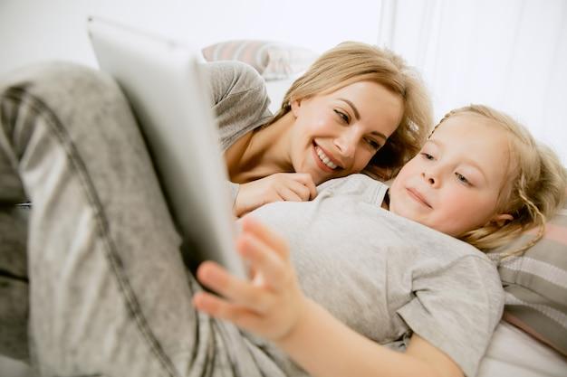 Jovem mãe e sua filha em casa na manhã ensolarada. cores pastel suaves. tempo feliz para a família no fim de semana. conceito de dia das mães. conceitos de família, amor, estilo de vida, maternidade e momentos ternos.